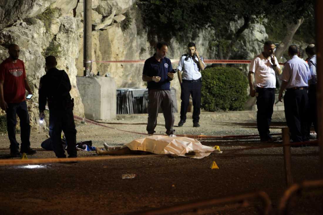 Israeliska poliser invid en av de tre angripare som sköts ihjäl utanför Jerusalems gamla stad.