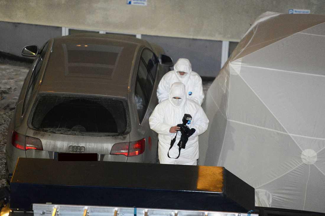 Två tekniker jämte tältet som spändes upp över den döde Markovic.