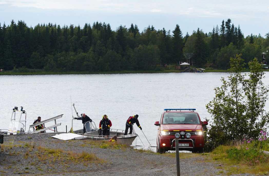 Räddningstjänsten tar i land en vrakdel. Ön där olyckan skedde syns i bakgrunden.