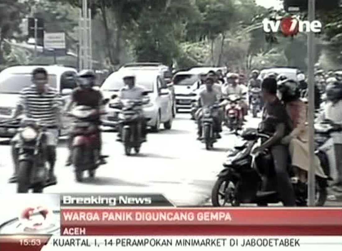 Tv-bilder visar hur folk flyr efter tsunamivarningen i Aceh.