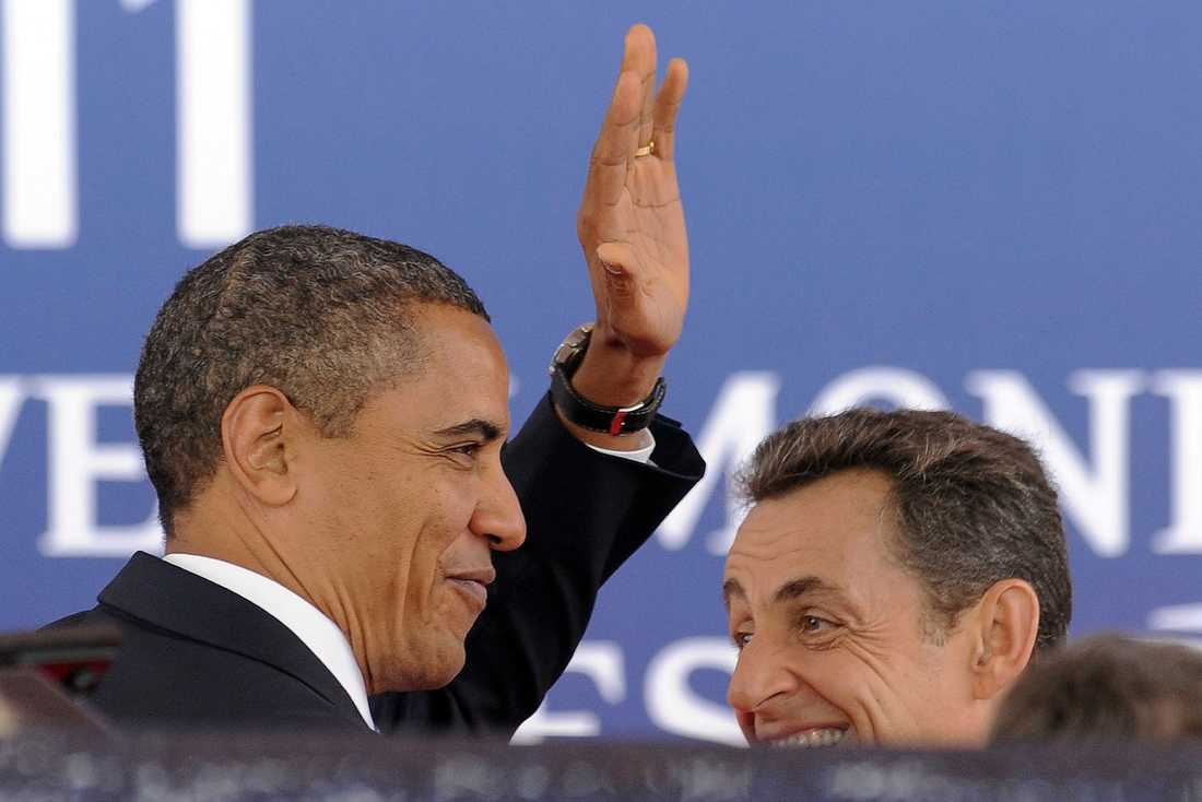 Glada, trots krisen. Obama och Sarkozy vinkade till åskådarna som samlats i Cannes för att få en skymt av världsledarna.