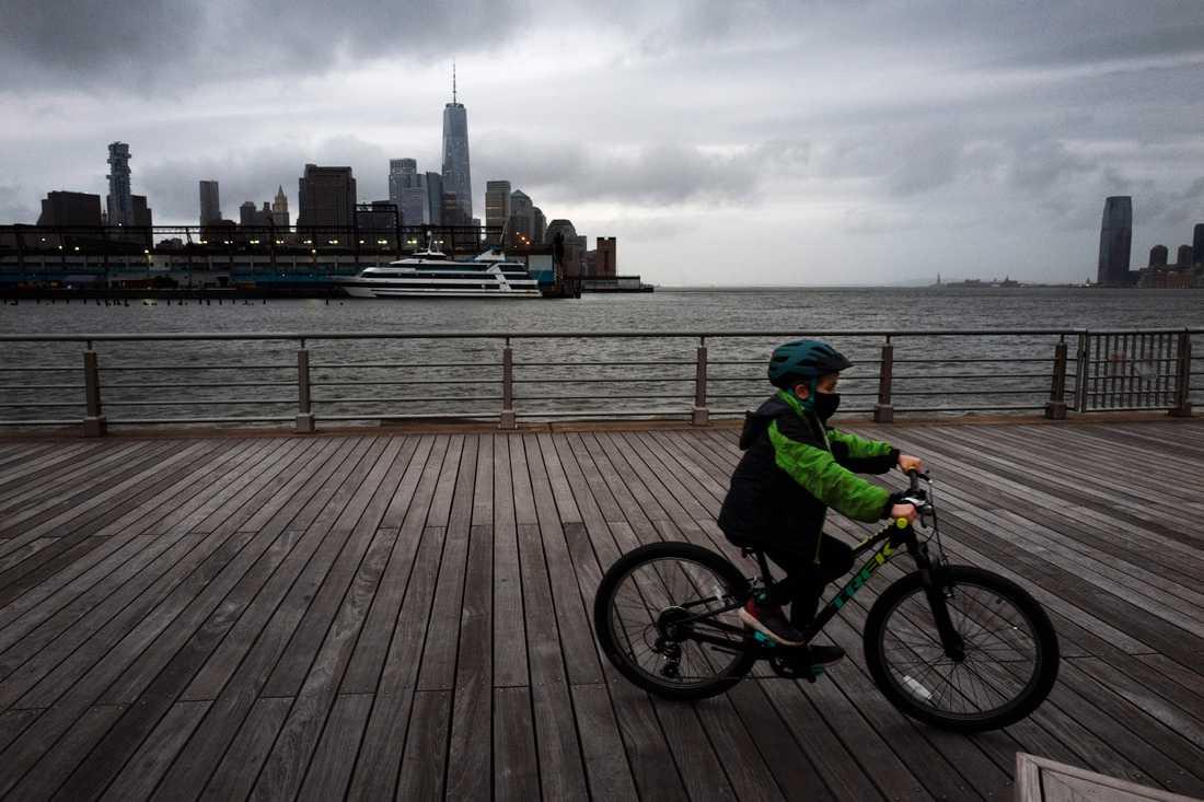 En pojke med ansiktsmask är ute och cyklar i Hudson River Park, New York. Pojken har inget med texten att göra.