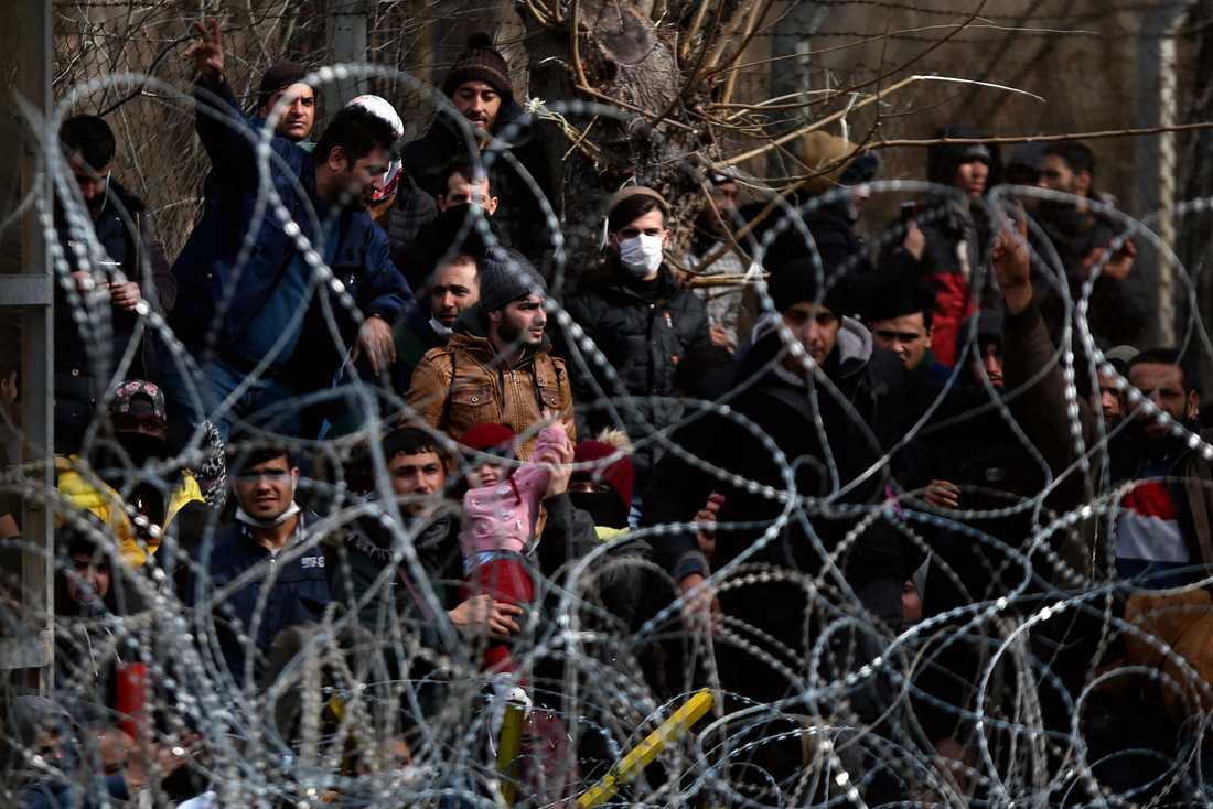 Migranter bakom en avspärrning nära den grekisk-turkiska gränsen i Kastanies.