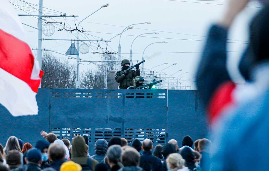 Belarusisk kravallpolis bevakar de tiotusentals demonstranter i huvudstaden Minsk som protesterar mot regimen under söndagen.