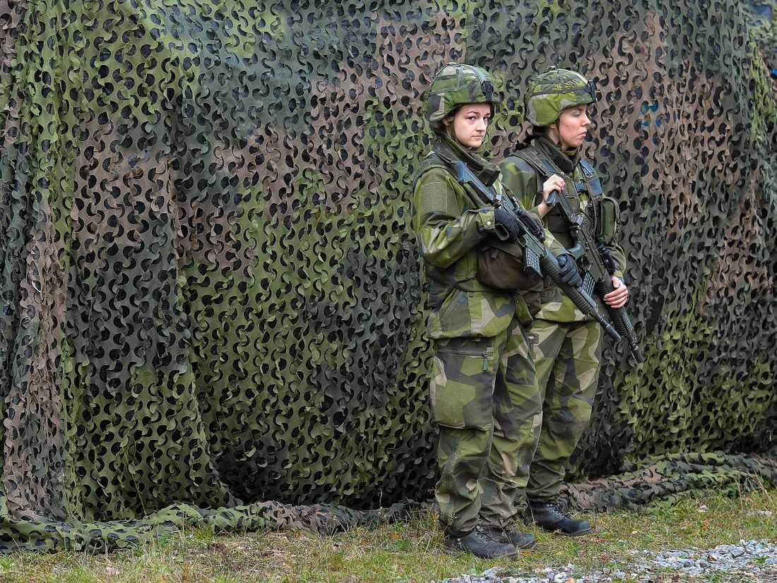 Militärfordon med skyddsnät vaktas av två soldater under försvarsövningen Aurora 17. Arkivbild.