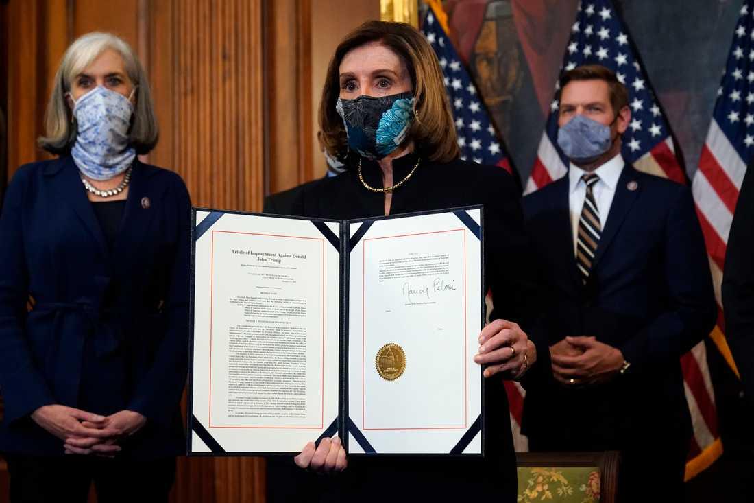 Nancy Pelosi visar upp underskriften.
