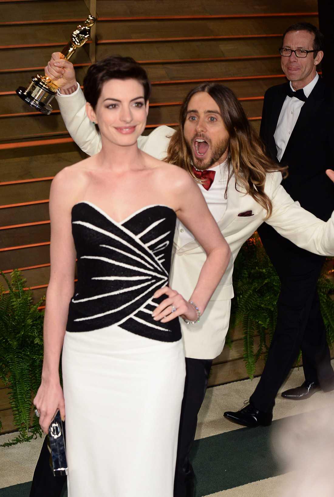 Här står Anne Hathaway och poserar. Helt ovetandes om att det står en galen Jared Leto bakom henne.
