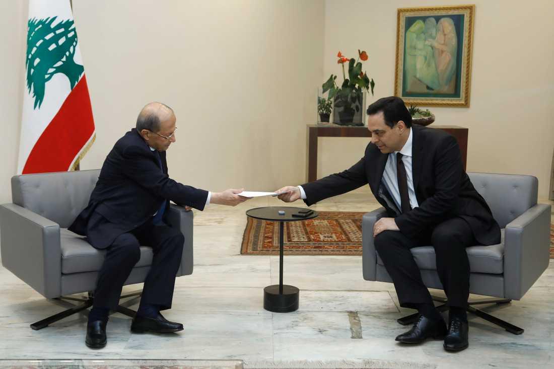 Libanons premiärminister Hassan Diab, till vänster, överräcker regeringens avgångsansökan till president Michel Aoun.