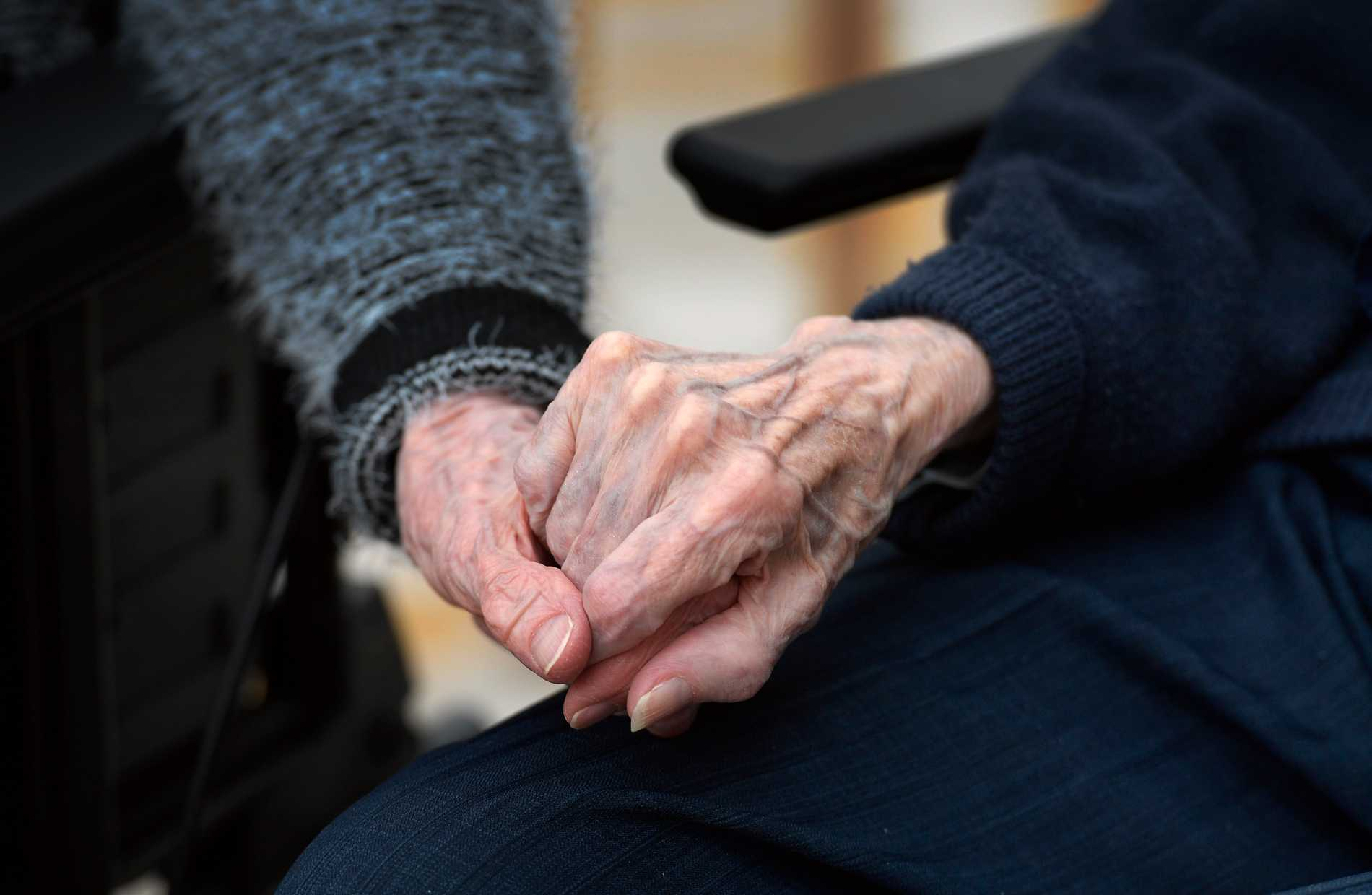 Två personer håller varandra i handen på äldreboende. Arkivbild.