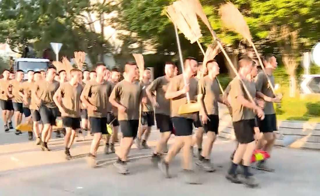 En bild från en videoupptagning visar kinesiska soldater med kvastar som anländer för att städa gator i Hongkong på lördagen.