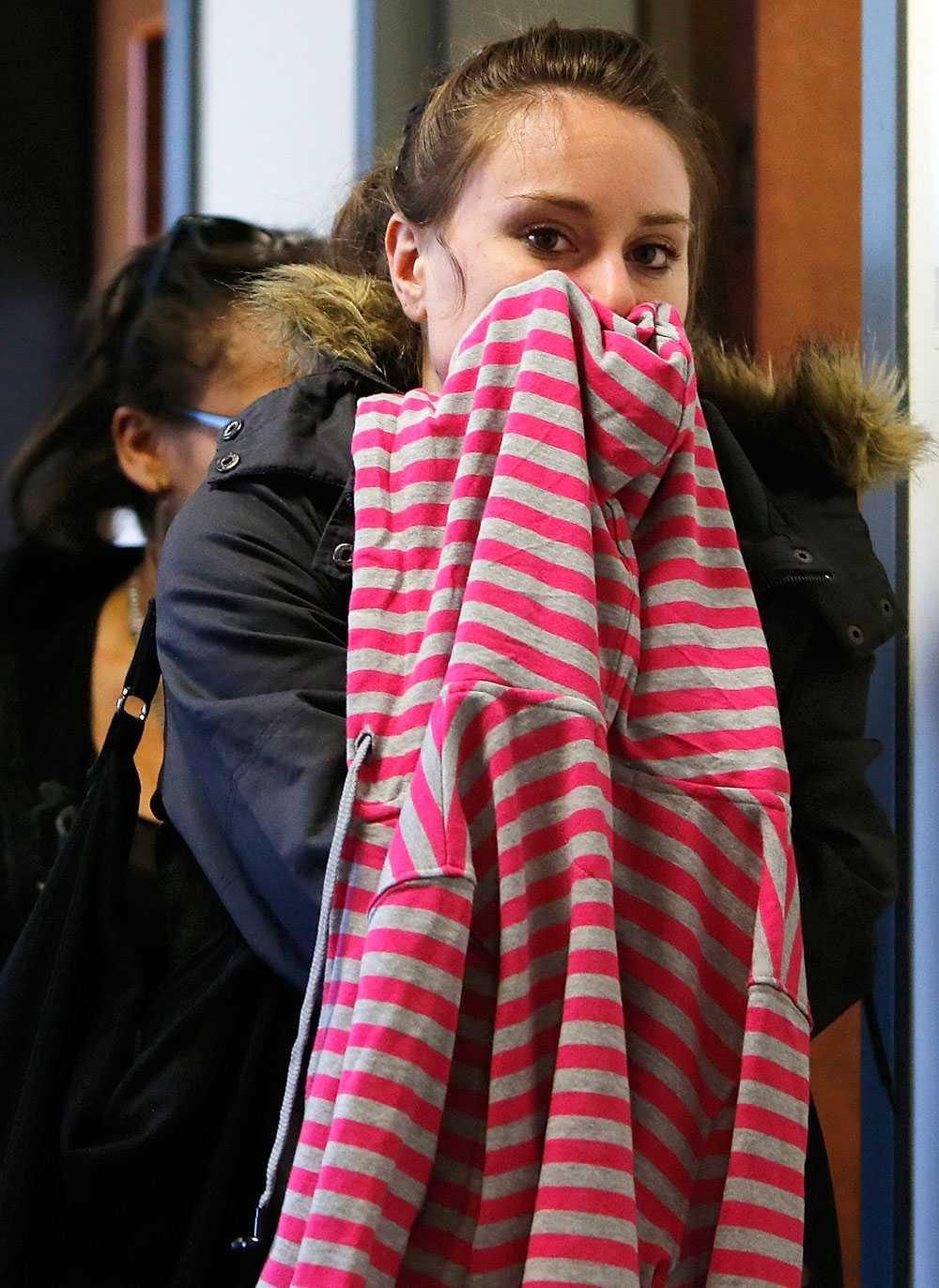 En ung kvinna döljer ansiktet efter att ha lämnat rättssalen.