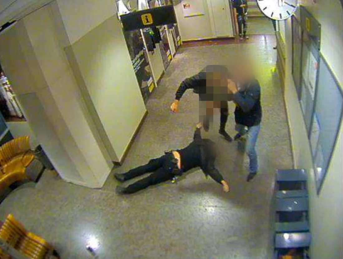 Mannen ses lyfta sitt ben för att sparka polismannen i huvudet samtidigt som en annan man ur gruppen försöker dra bort honom.