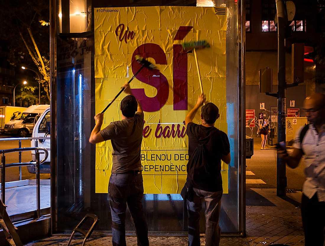Barcelonabor klistrar upp affischer om valet i morgon. Den spanska regeringen har förbjudit spridande av information och reklam för folkomröstningen.