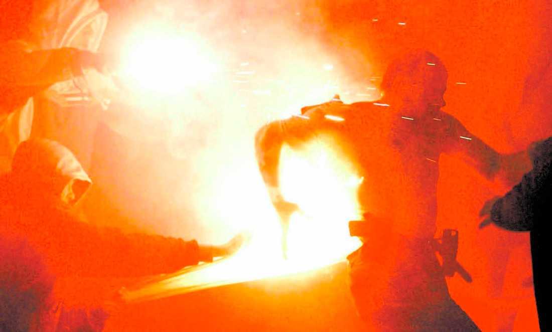 GICK TILL ANFALL Röda Stjärnans fans gick till attack mot polisen. Här skadas en polis när han bränns av en bengal.