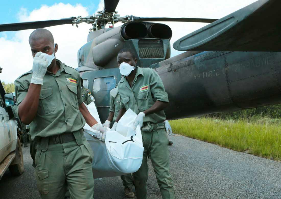 Personal lastar av en kropp från en militärhelikopter i Chimanimani,  600 km sydöst om Harare, Zimbabwe.