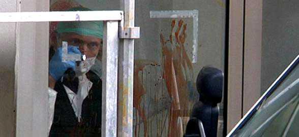 Polisens tekniker tittar på ett blodigt handavtryck.