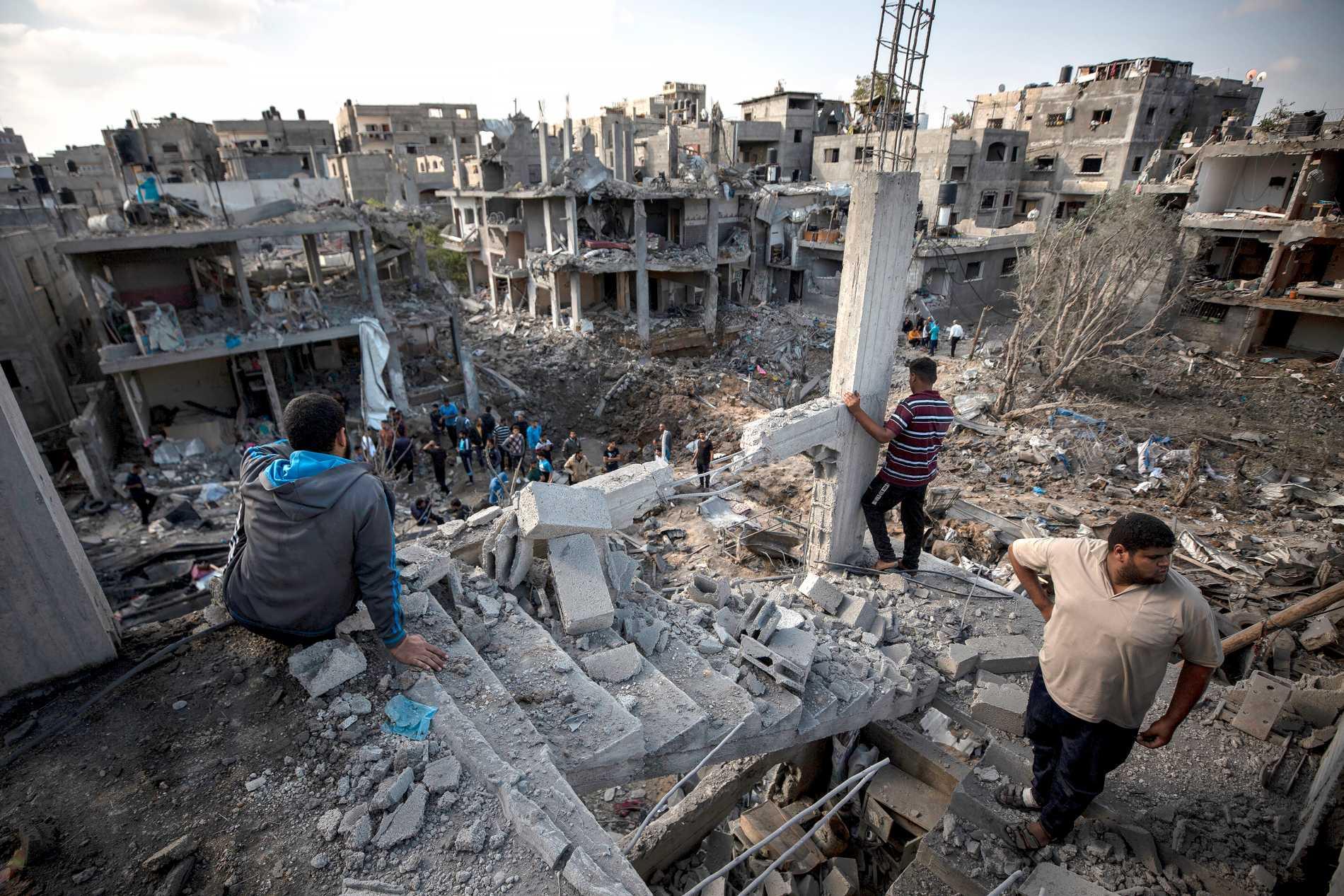 Palestinier vid sina förstörda hus i Beit Hanoun, norra Gaza efter israeliska attacker natten mot fredag.