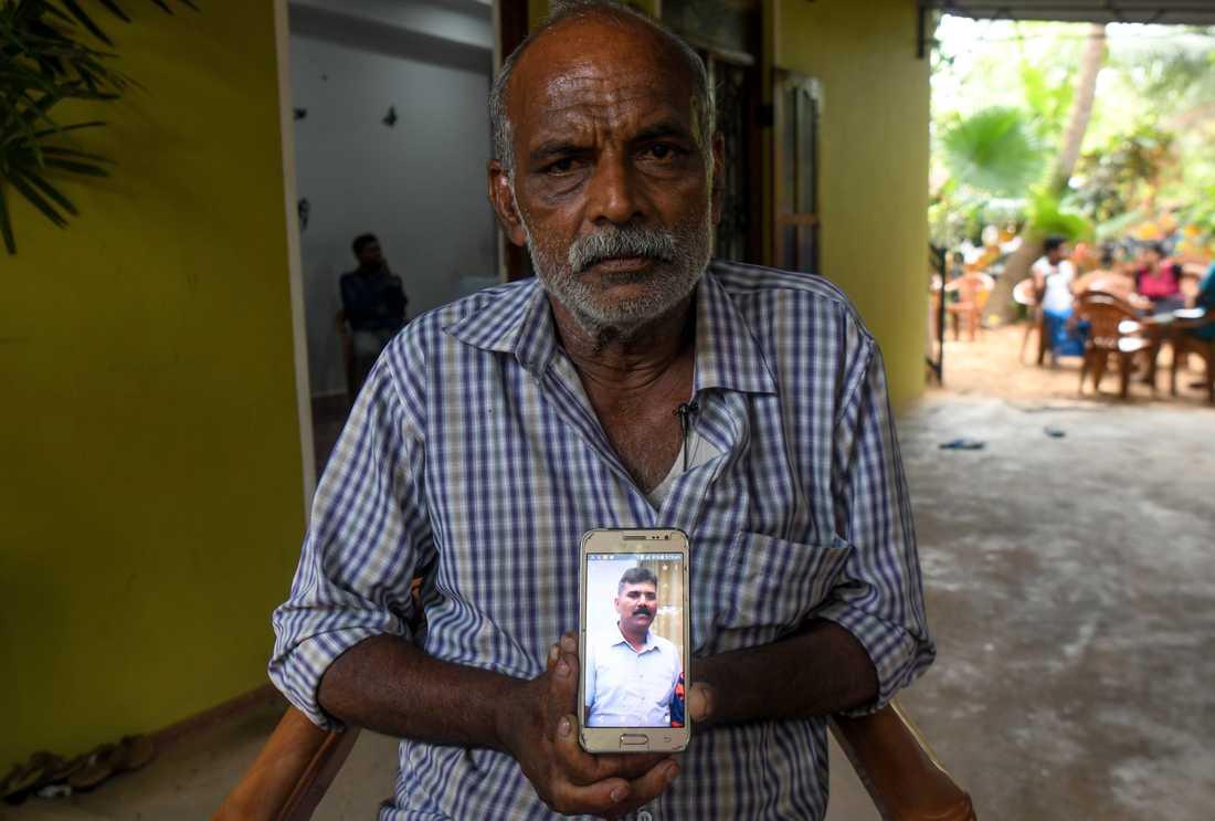 Velusami Raju, Ramesh Rajus pappa, håller upp en bild på sonen.