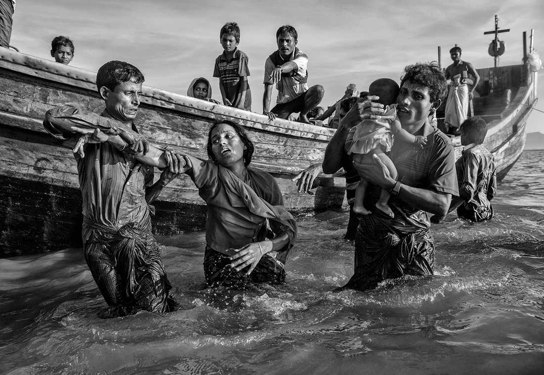En utmattad kvinna får hjälp av en båt vid Shah porir Dwip efter att ha flytt Burma över floden Naf.