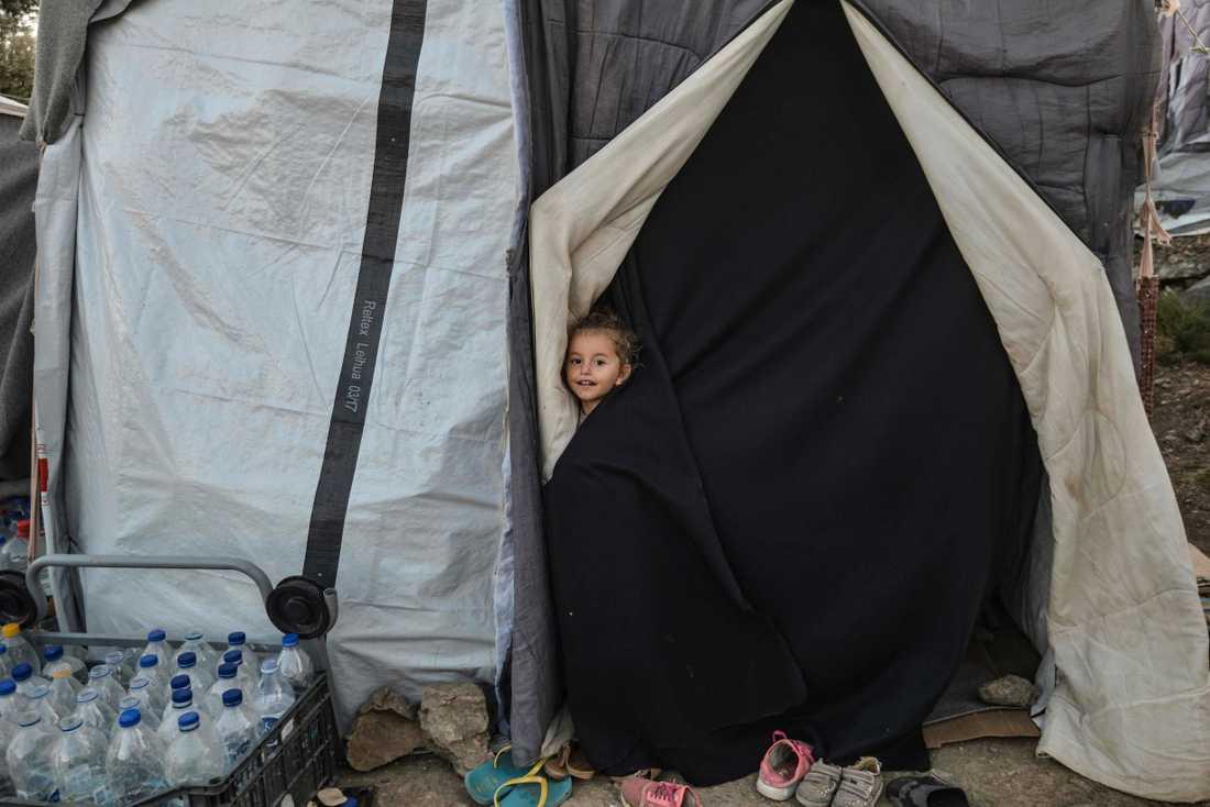 En flicka kollar ut från ett tält i flyktinglägret Moria på grekiska ön Lesbos. Lägret har plats för 3000 människor men för tillfället är det uppehåll för cirka 8000 flyktingar.