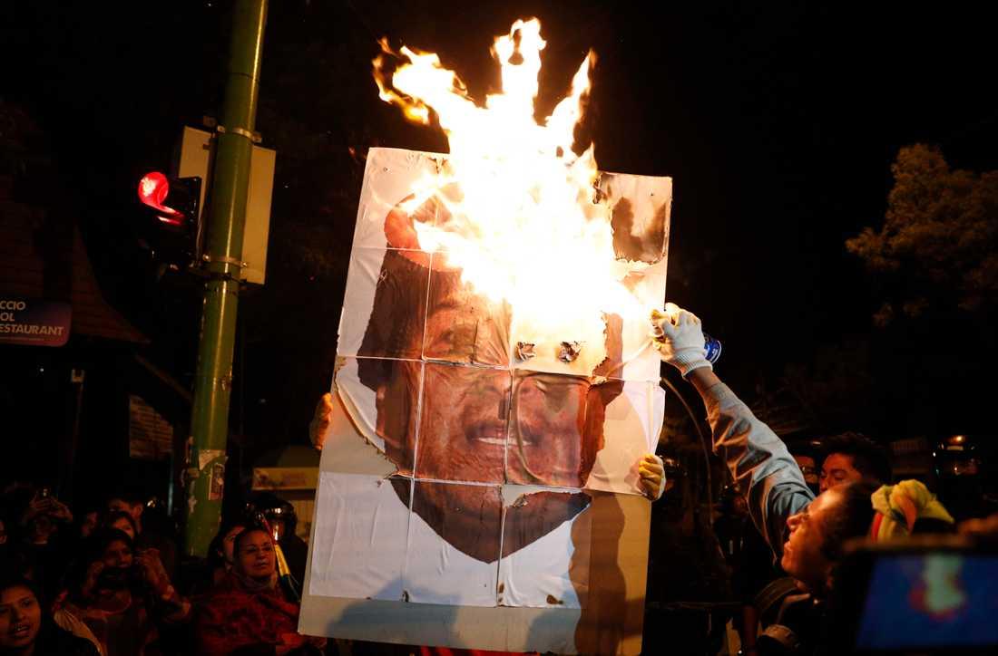 Demonstranter bränner en bild av president Evo Morales i Bolivias huvudstad La Paz den 26 oktober.