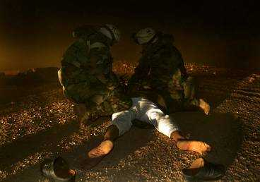 GREP IRAKIER - PÅ BASEN Två amerikanska soldater på en bas i södra Irak sätter handklovar på en irakier. Mannen hade lyckats ta sig fram till utkanten av basen i skydd av sandstormen när han greps. Samtidigt rapporterades en stor irakisk militärkonvonj vara på väg mot de amerikanska styrkorna i Najaf. Konvojen utsattes för hårda bombangrepp från B-52-plan.
