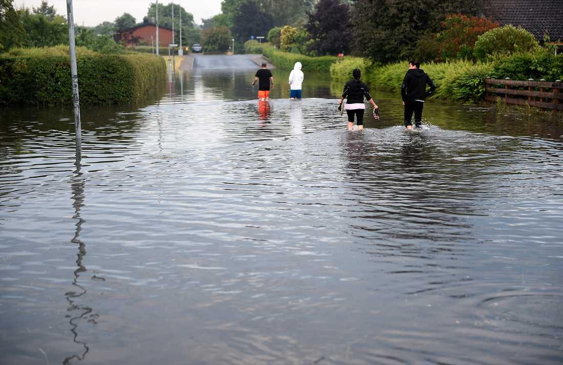Människor vadar genom vattnet på Astergatan i ett översvämmat Bjuv efter att kraftiga åskskurar drabbat södra Sverige på onsdagen.