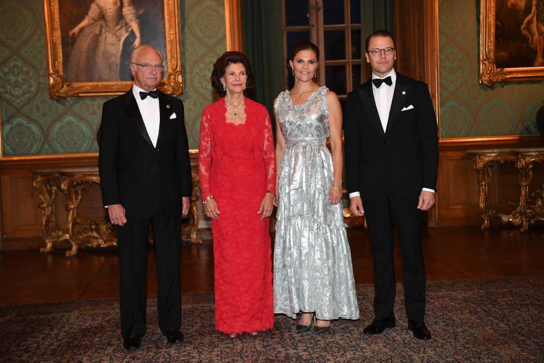 Drottning Silvia i traditionell klänning och kronprinsessan Victoria i klänning från H&M.