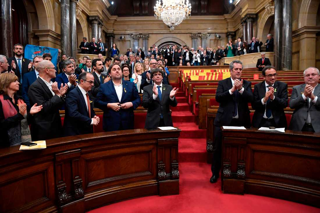 Kataloniens president Carles Puigdemont applåderar efter omröstningen.
