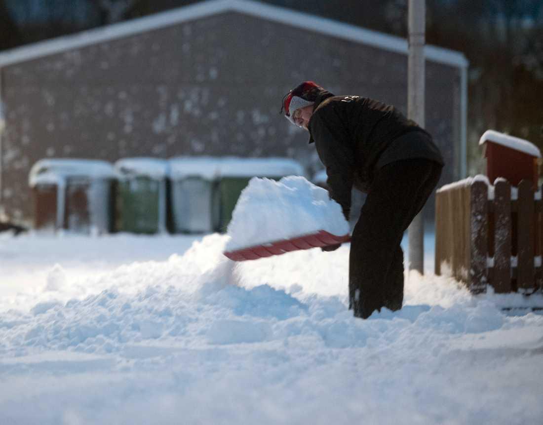 En mann skottar snö i Enköping.