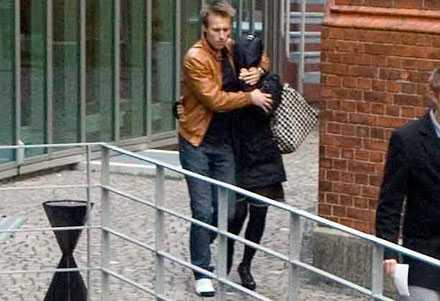 Carola Häggkvists ansikte täcks över av en man medan de lämnar Ystads tingsrätt bakvägen efter vittnesmålet på onsdagen.