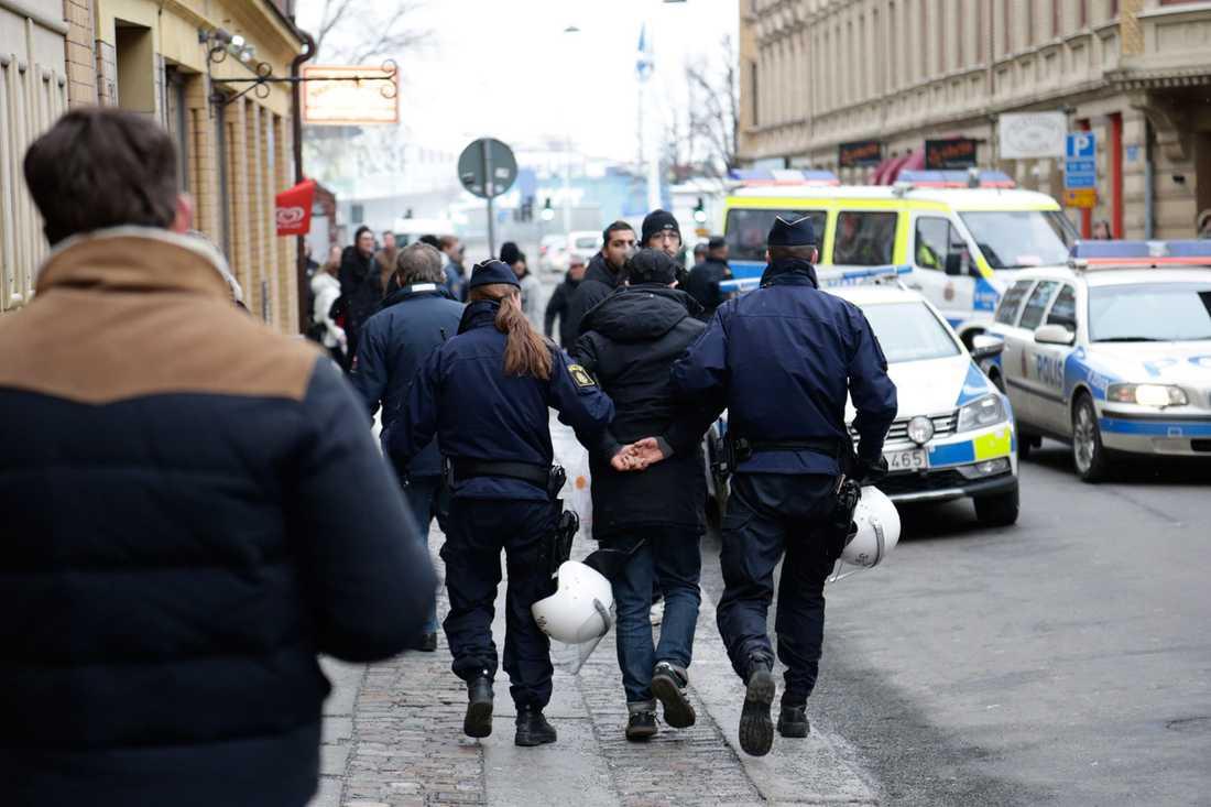 En kille förs bort av polis.