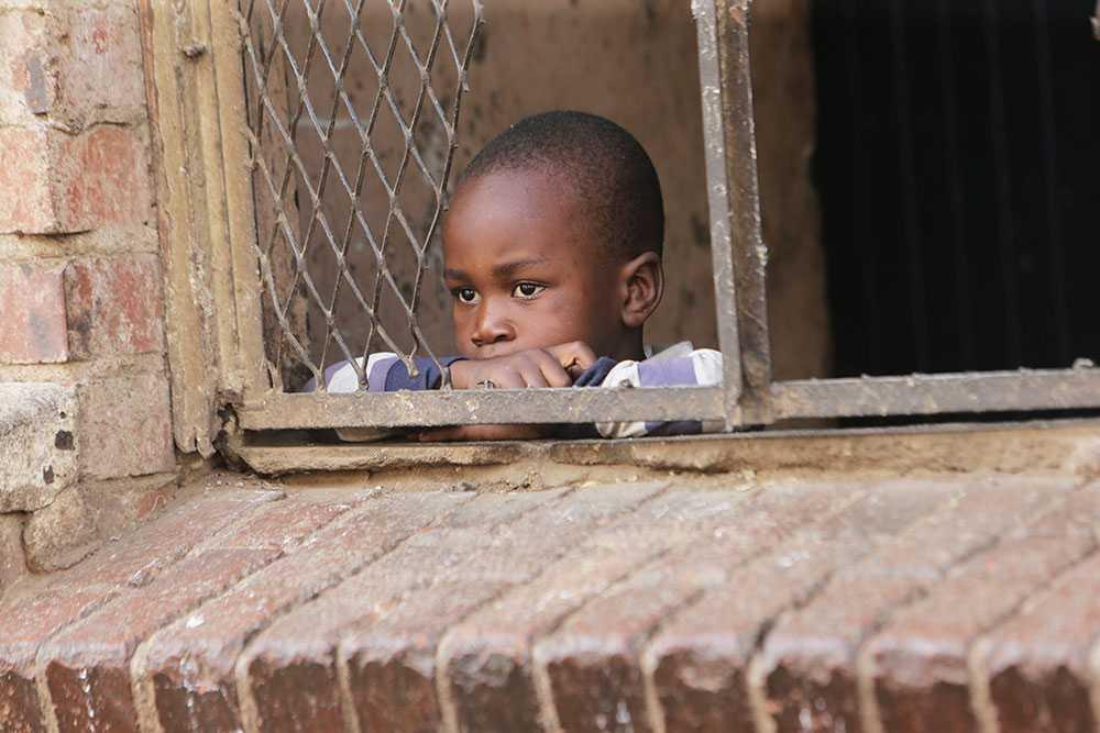 Ett litet barn tittar ut i ett nerstängt Harare, Zimbabwe, där bristerna inom vården är stora.
