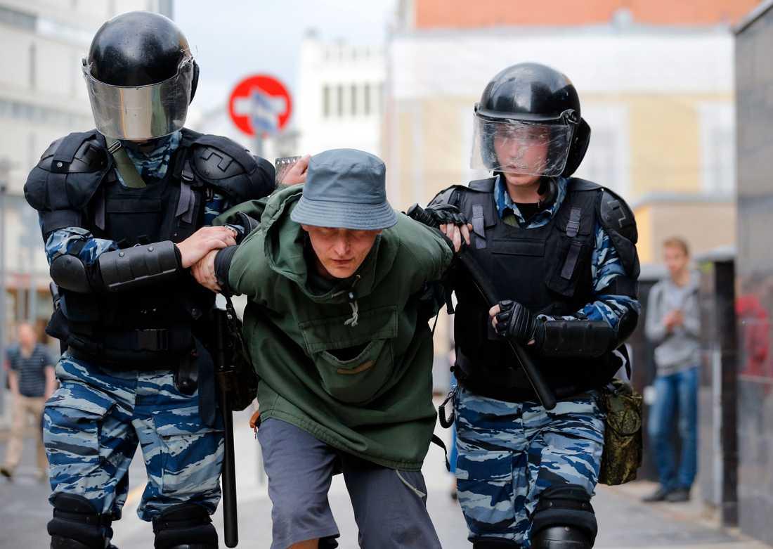 En man förs i väg av polisen i Moskva i samband med protesterna.