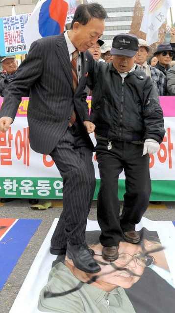 Protestanter trampar på ett porträtt av Nordkoreas ledare Kim Jong-Il i Seoul.