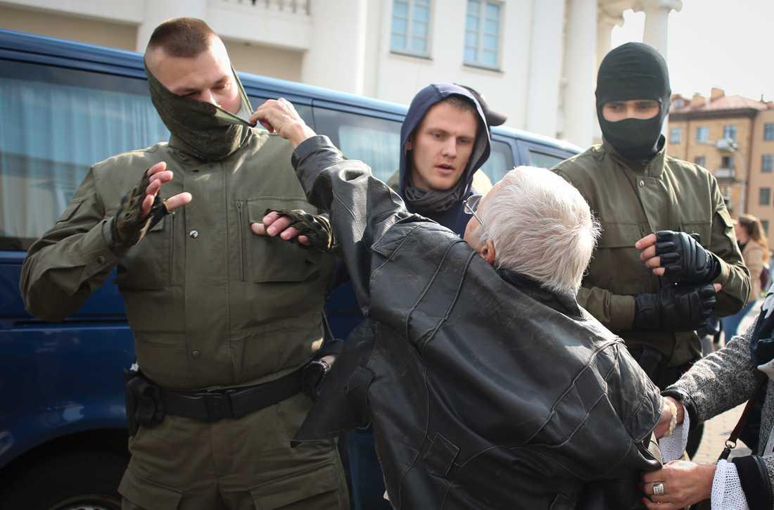 En kvinna försöker slita maskeringen av en polis sedan en patrull ingripit och försökt gripa demonstranter.
