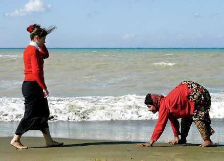 möte En av de fyra systrarna möter en kvinna på stranden.