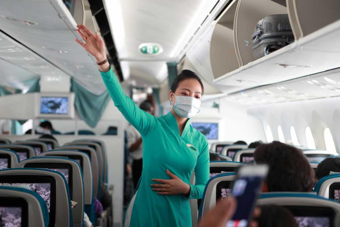 Flygvärdinna med skyddsmask instruerar passagerare på flygplan i Ho Chi Minh-staden i Vietnam. Arkivbild.