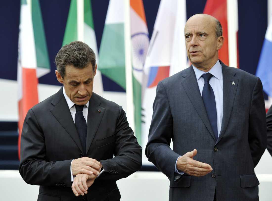 Sarkozy kollar klockan, samtidigt som hans utrikesminister Alain Juppe talar.