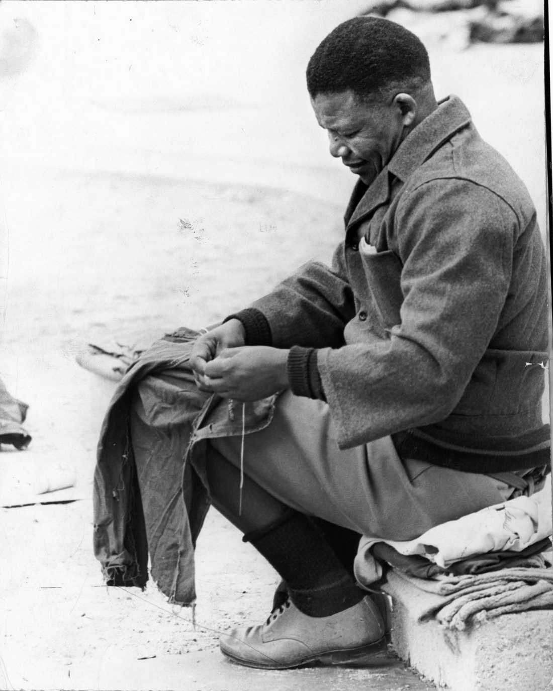 """April 1965. Nelson Mandela i fängelset på Robben Island.  Nelson Mandela fängslades på ön Robben Island där han fick tillbringa de följande 18 åren. Under sin tid i fängelse lyckades Mandela hålla kontakt med ANC, som publicerade ett uttalande om Mandela den 10 juni 1980 där det bland annat stod: """"Förena! Mobilisera! Fortsätt kampen! Mellan städet av en förenad massaktion och hammaren som är den väpnade kampen kommer vi att krossa apartheid!"""""""