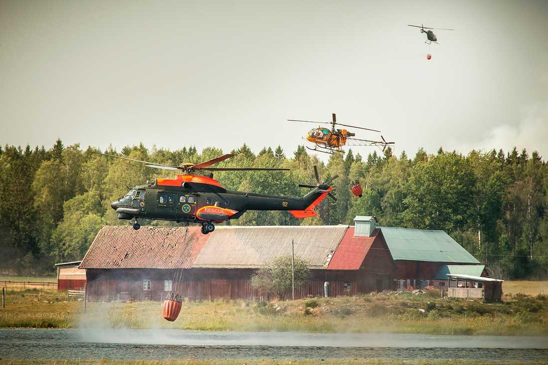 Helikoptrar hämtar vatten för att bekämpa branden i Sala.