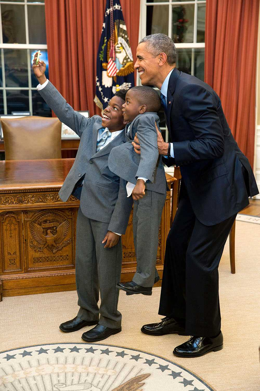 """Pete Souzas kommentar: """"Presidenten går utan protest med på att ta en selfie med 11-årige Jacob Haynes och 4-årige James Haynes efter att ha tagit ett familjefoto med avgående stabskollegan Heather Foster 2015"""
