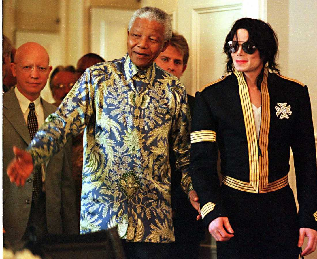 President Nelson Mandela tillsammans med King of pop, Michael Jackson. De är på väg till en presskonferens i Kapstaden i mars 1999 där Michael Jackson offentliggjorde två konserten till stöd för Nelson Mandela Children's Fund.