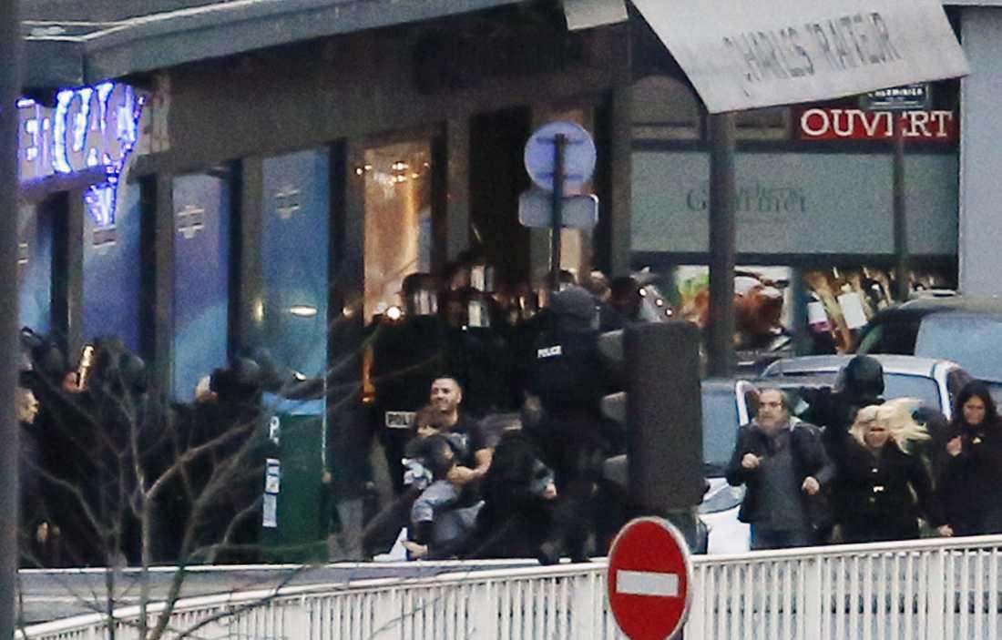 Polis evakuerar gisslan ur butiken i Paris.