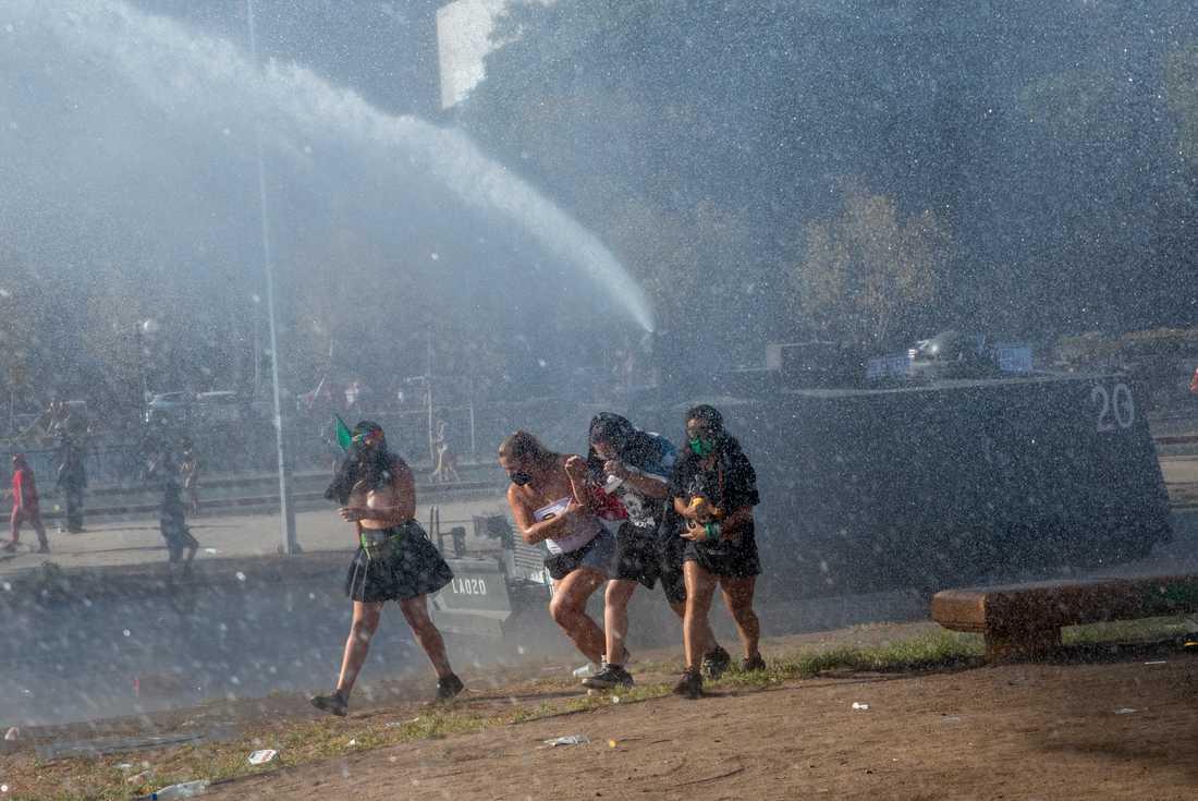 Demonstranter springer från polisens vattenkanon i Chiles huvudstad Santiago på den internationella kvinnodagen den 8 mars.