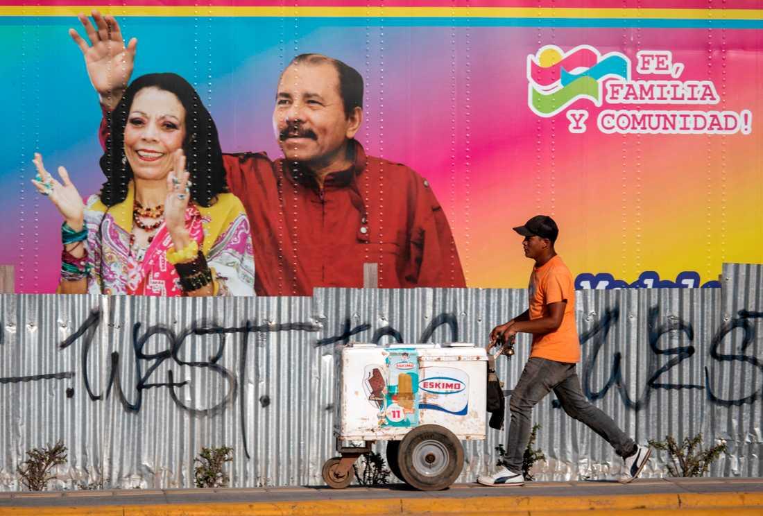 En glassförsäljare går förbi en mobil vårdinrättning med ett portträtt av Nicaraguas president Daniel Ortega och hans fru, vicepresident Rosario Murillo.