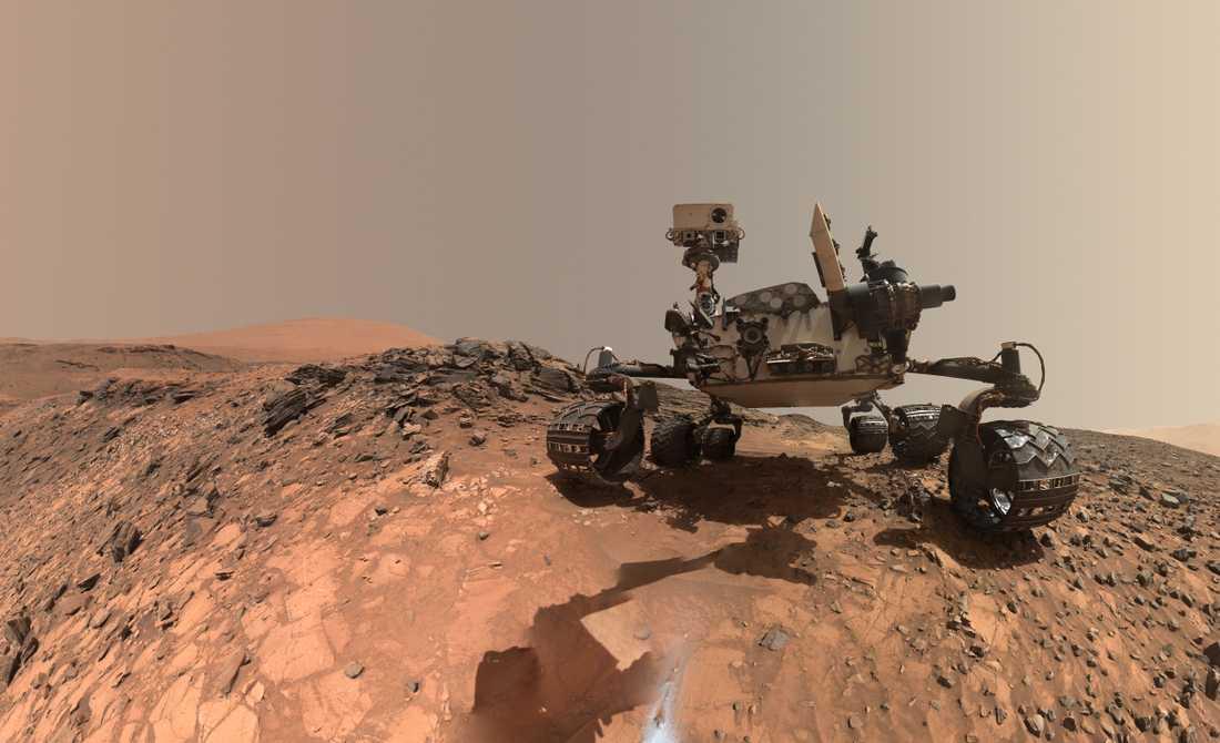 Marsroboten Curiosity rullar runt på Mars sedan augusti 2012 och skickar då och då selfies till jorden. De är tagna med hjälp av robotens arm, som sedan har retuscherats bort från bilden.