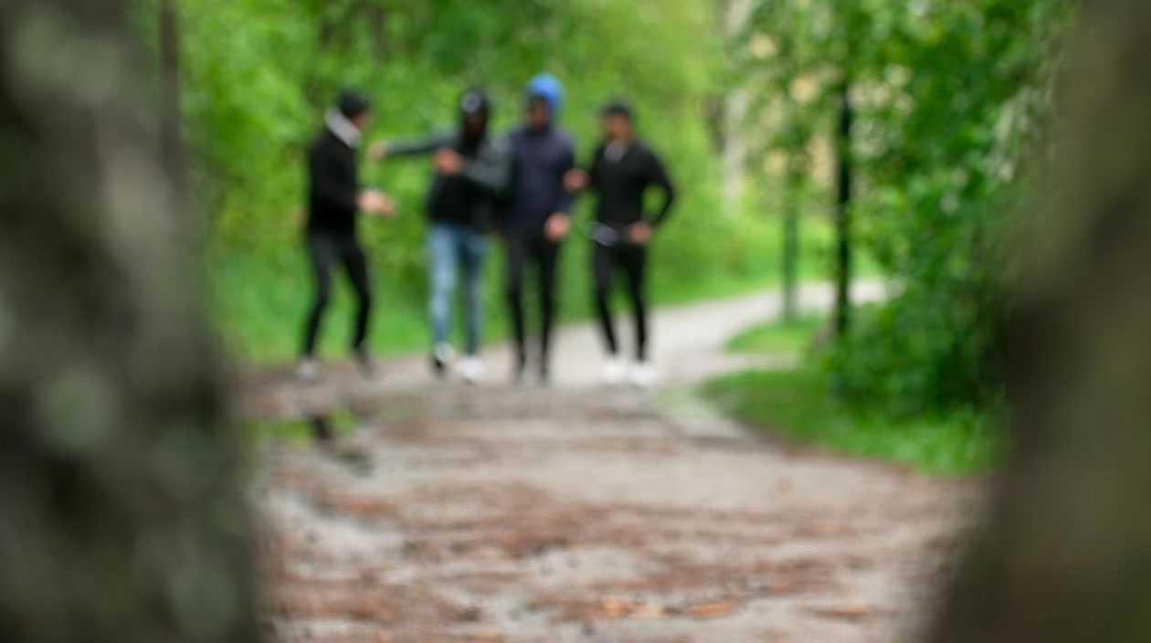 Fyra unga män gick i bredd på vägen rakt mot henne.