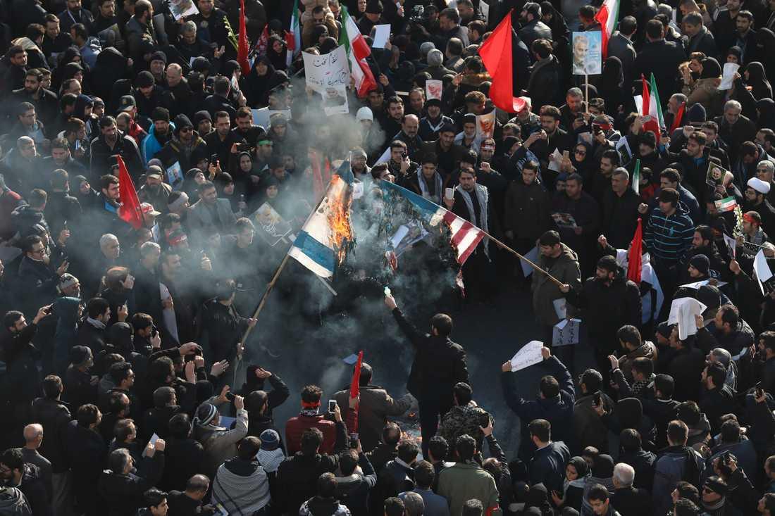 Israels och USA:s flagga bränns i folksamlingen i Teheran.