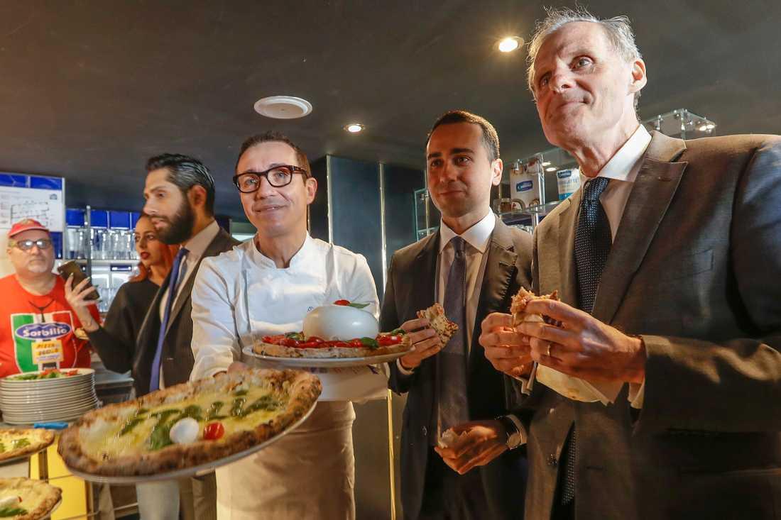"""Italiens utrikesminister Luigi Di Maio, i mitten, äter pizza tillsammans med Frankrikes Romambassadör Christian Masset. Di Maio bjöd in ambassadören till pizzalunch sedan en fransk tv-kanal sänt ett kritiserat satirinslag om """"coronapizza""""."""